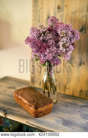 Bouquet Of Lilac Stands With Homemade Rye Yeast-free Bread On The Table