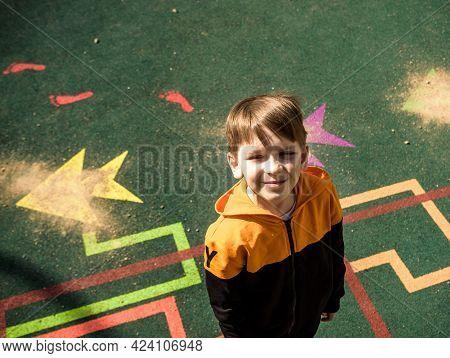 Boy Playing On The Playground, In The Children's Maze. Children's Slide