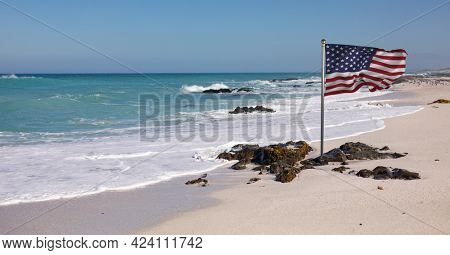 Composition of waving american flag against blue sky and seaside. united states of america flag, patriotism and independence concept digitally generated image.