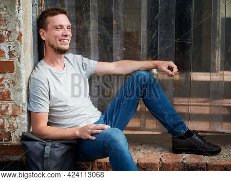 Smiling Male Sitting On Stairs Of Abandoned House. Young Man In Grey T-shirt And With Bag Is Resting