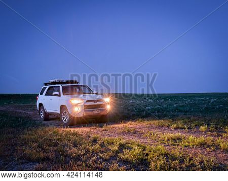 Keota CO, USA - June 14, 2021: Toyota 4Runner SUV (2016 Trail edition) before sunrise in Pawnee National Grassland in northern Colorado, late spring scenery with green grass and wildflowers.