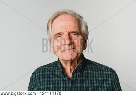 Elderly Caucasian man with white hair smiling on gray background