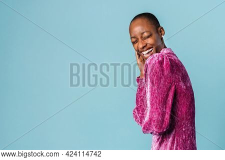 Cheerful black woman in a pink dress