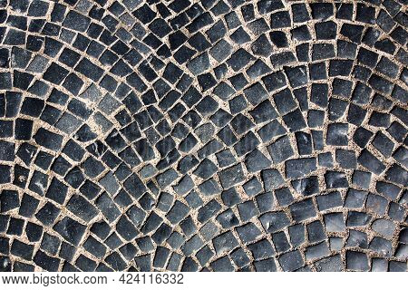 Paving Stones, Road Is Paved With Black Square Tiles. Stone Texture, Grunge Background.