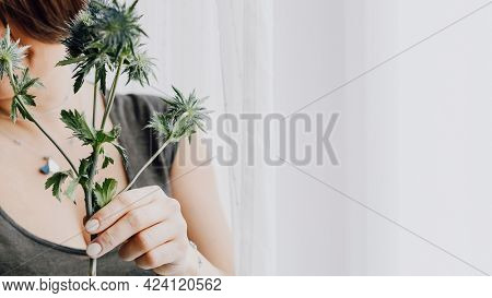 Woman holding a blue thistle