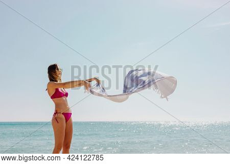 Girl in a pink bikini with a towel at the beach