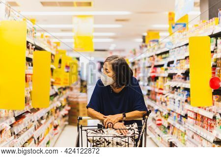 Senior Woman In  Protective Mask Shopping In Supermarket Alone