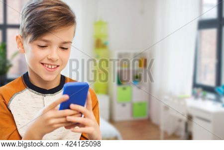 leisure, children, technology, internet communication and people concept - smiling boy with smartphone texting message or playing game at home over children's room background