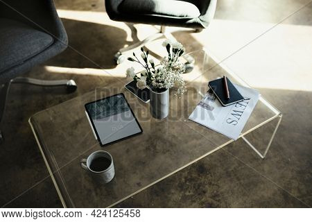 Digital tablet mockup by a vase with white carnation flowers