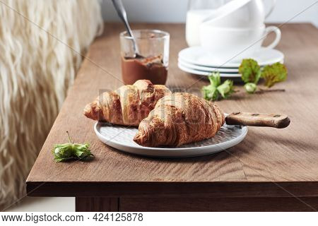 Two Croissants With Chocolate Cream And Hazelnuts On A Wooden Table.
