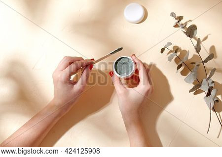 beauty, cosmetics and bodycare concept - hands holding jar of blue cosmetic clay mask and wooden spatula over branch of eucalyptus populus on beige background