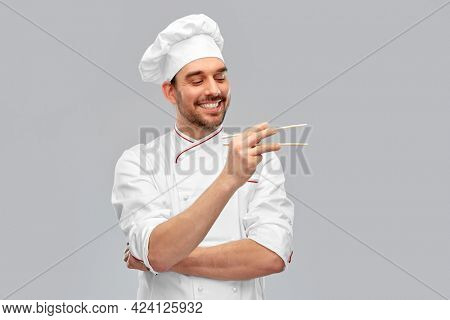 food cooking, asian cuisine and people concept - happy smiling male chef in toque holding something with chopsticks over grey background