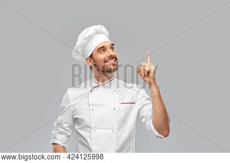 cooking, culinary and people concept - happy smiling male chef in toque pointing finger up to something over grey background