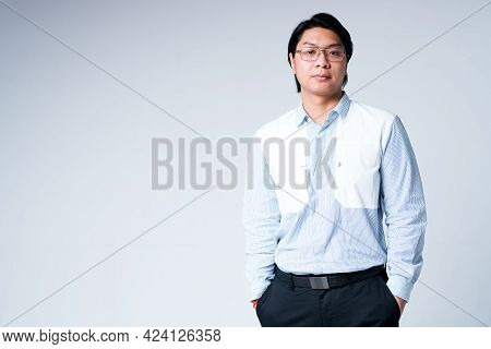 Handsome Young Asian Businessman In Shirt And Glasses Stands On White Background With Hands In Pocke