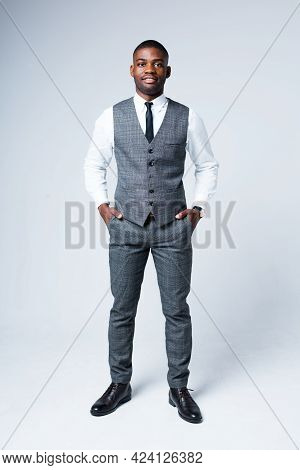 Full-length Photo. Handsome Smiling African American Businessman In Suit Stands With Hands In Pocket