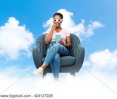 cinema, entertainment and people concept - happy african american woman in 3d movie glasses eating popcorn from striped bucket sitting in armchair over blue sky and clouds background