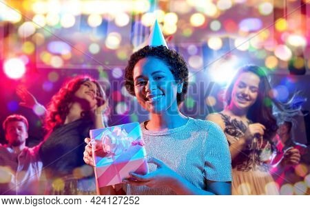 birthday, celebration and nightlife concept - happy smiling young african american woman in party cap with gift box in ultraviolet neon lights over nightclub background