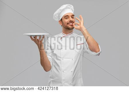 cooking, culinary and people concept - happy smiling male chef in toque holding empty plate over grey background