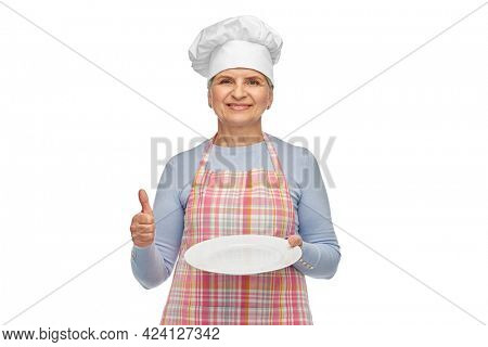 cooking, culinary and old people concept - portrait of smiling senior woman or chef in toque in kitchen apron holding empty plate showing thumbs up over white background