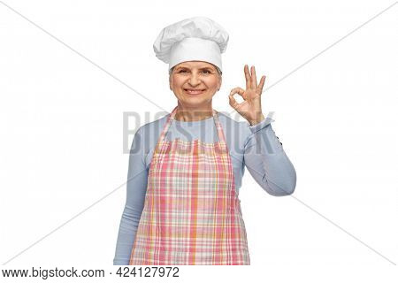 cooking, culinary and old people concept - portrait of smiling senior woman or chef in toque in kitchen apron showing ok hand sign over white background