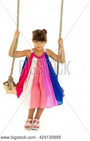 Cute Girl Having Fun On Wooden Swing. Lovely Girl Swinging Against White Background. Full Length Sho
