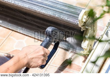 Cleaning Air-conditioner. Spraying Water To Clean The Indoor Air Conditioner. Cleaning Air Condition