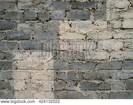 Background From Old Gray Rough Brick Wall. The Top Is Painted With Beige Paint. Cement Joints. The T