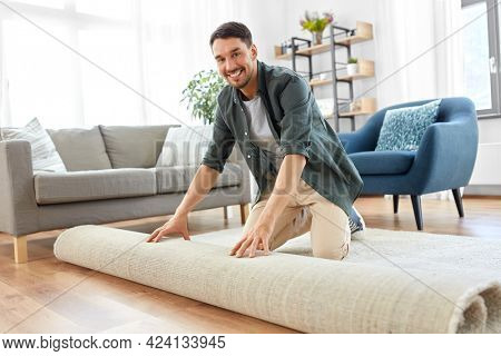 home improvement, interior and real estate concept - happy smiling young man unfolding carpet