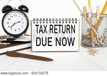 Tax Return Due Now. A Notebook On A Work Table, Near A Desk Clock, A Flowerpot And A Glass With Penc