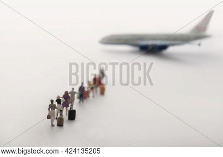 Miniature People In Queue Ready To Board Aeroplane