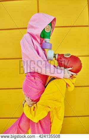 Two lovers in colorful clothes and gas masks seek salvation from a technological disaster. Global environmental disaster.