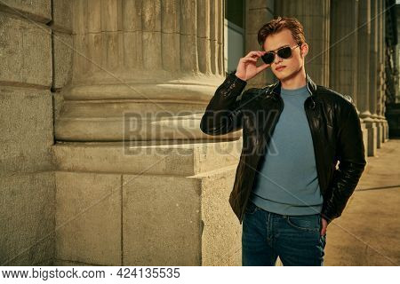 Handsome confident young man in sunglasses and leather jacket walks along the city street against the background of an old building. Men's fashion. Lifestyle.