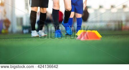 Selective Focus To Leg Of Boy Soccer Players Jogging On Green Artificial Turf For Training.
