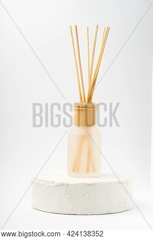 Aroma Bottle Glass And Wooden Sticks Staying On Cement White Podium On White Background