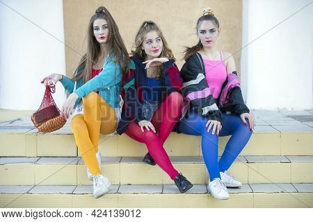 Three Pretty Girls Dressed In The Style Of The Nineties Are Sitting On The Steps.
