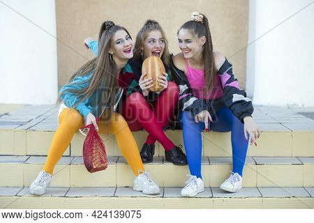 Three Pretty Girls Dressed In The Style Of The Nineties Are Sitting On The Steps And Sharing A Roll.