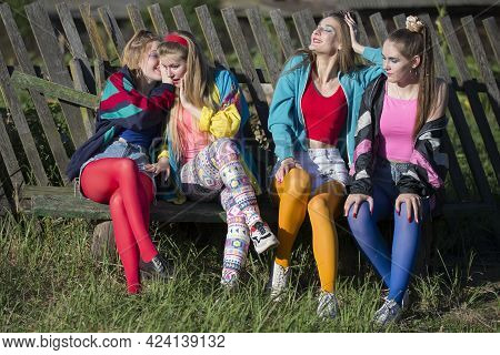 Pretty Girls Dressed In The Style Of The Nineties Sit On A Bench By A Skewed Fence.