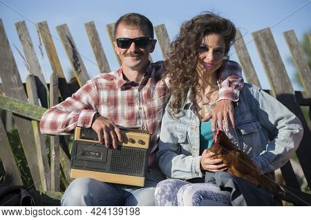 A Girl With A Chicken And A Man With A Retro Magnetophone Are Sitting On The Bench. The Villagers Ar