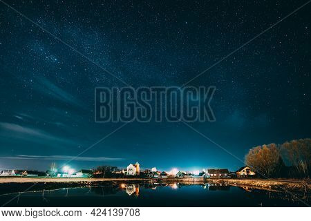 Belarus, Eastern Europe. Night Sky Stars Above Countryside Landscape With Lake Coast And Small Town
