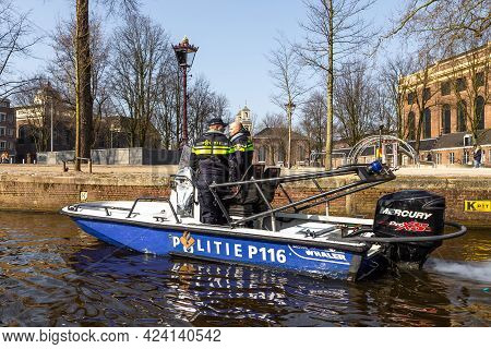 Amsterdam, Netherlands - 12 March 2016: Dutch Police Patrol On A Motorboat. Typical Dutch Houses. Ci