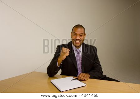 Black Man With Pad At Desk With Raised Fist