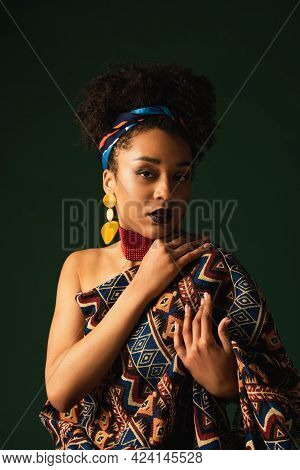 African American Woman In Headscarf, Earrings And Necklace Sitting Wrapped In Ornament Blanket On Da