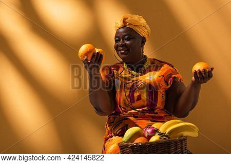 Positive Middle Aged African American Saleswoman Holding Oranges In Hands And Selling Fruits On Back