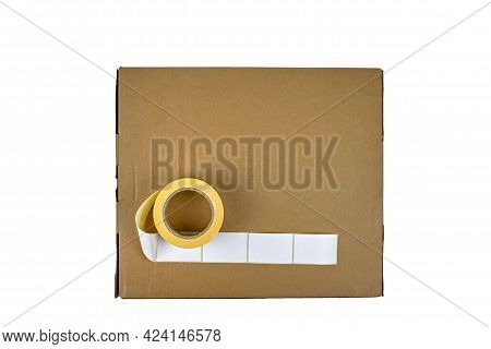 Stickers On A Cardboard Box, Isolate On A White Background. Sticky White Labels. Roll Of White Stick