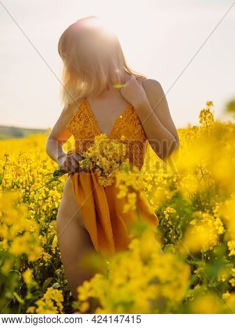 Portrait Of Attractive Woman On Rapeseed Field With Sunset Light. Yellow Flowers And Nude Woman
