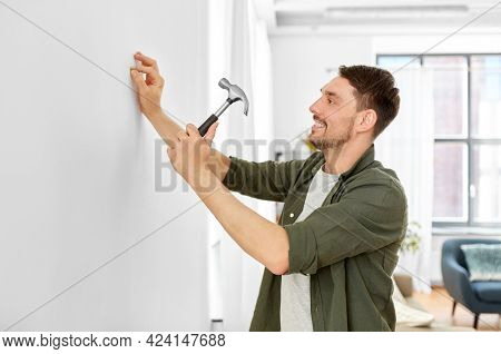 home improvement, repair and people concept - happy smiling man hammering nail to wall