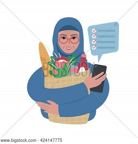 Senior Woman Wearing A Headscarf With Groceries Bag And A Shopping List On A Smartphone.