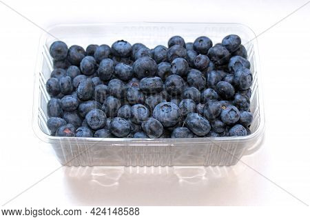 Fresh Ripe Organic Blueberries Fruit Pile In Plastic Container Isolated On White Background