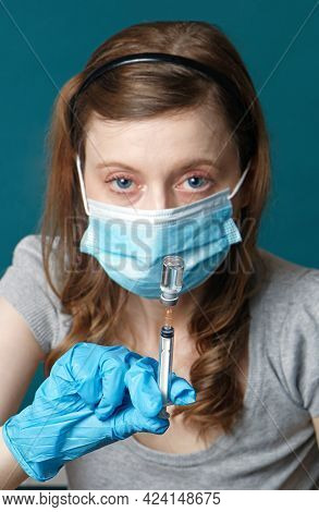 Young Nurse Wearing Face Mask And Medical Glove Holding Full Vial On A Syringe