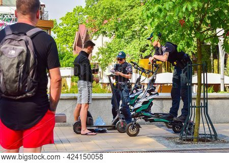 Palanga, Lithuania, 10th June, 2021: Female Police Officer Gives Penalty To Civilian On Scooter In P